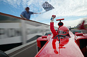 Formula One Driver Raising His Fist in Celebration as He Passes a Man Waving a Chequered Flag