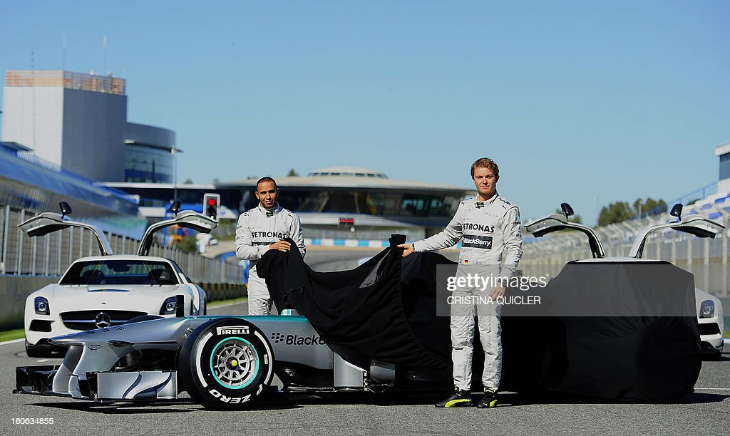 Formula One drivers, German Nico Rosberg (R) and British Lewis Hamilton (L) unveil the new Mercedes W04 as part of the Formula One training session at Jerez racetrack, on February 4, 2013 in Jerez de la Frontera. AFP PHOTO/ CRISTINA QUICLER