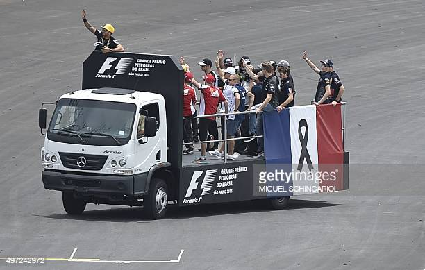Formula One drivers parade atop a truck with a French flag decorated with a black ribbon in homage to the victims of the terrorist attacks in Paris...