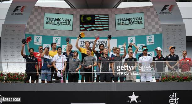 Formula One drivers pose for a farewell group photograph before the start of the Formula One Malaysia Grand Prix in Sepang on October 1 2017 / AFP...