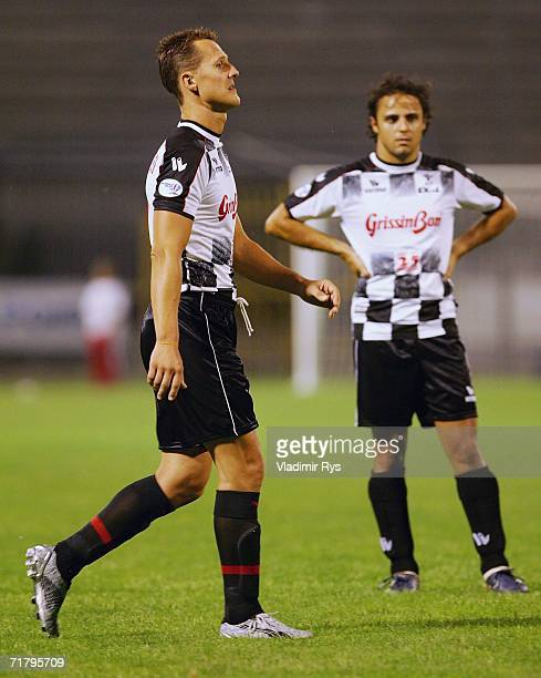 Formula One racing driver Michael Schumacher of Germany and his team mate Felipe Massa of Brazil and Ferrari wait for the start of the benefit match...