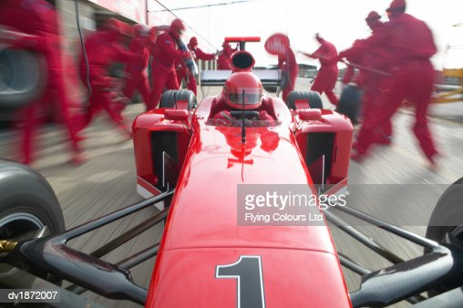 Formula One Racing Driver Quickly Pulling Away from a Pit Stop on a Motor Racing Track : Stock Photo
