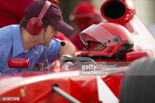 Formula One Racing Driver Talking with a Man Wearing a Headset During a Pit Stop : Stock Photo