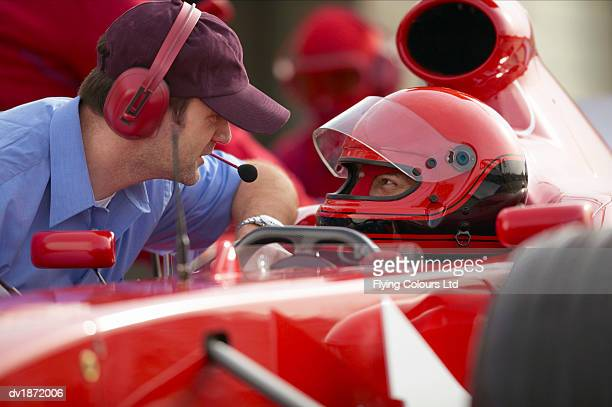 Formula One Racing Driver Talking with a Man Wearing a Headset During a Pit Stop