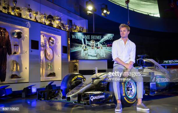 Formula One World champion Nico Rosberg poses for photographers on his car during the transfer of his world championship car a Mercedes F1 W07 hybrid...
