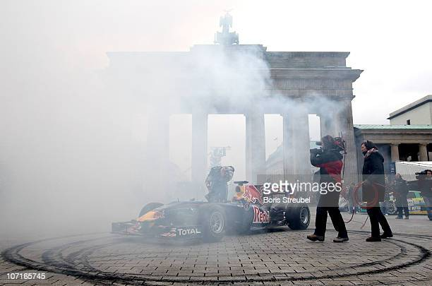 Formula One world champion Sebastian Vettel gets out of his Formular One car after turning donuts during his visit at Brandenburg Gate on November 27...