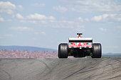 Formula race car cresting hill on race course.