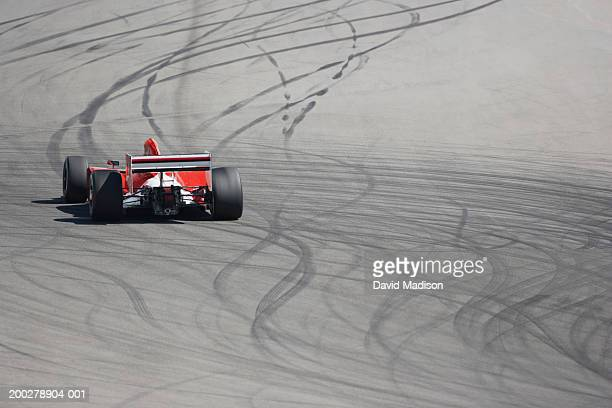 Formula racing car driving over skid marks on track, rear view