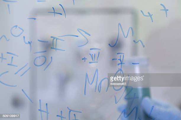 Formulas on glass pane in chemical laboratory