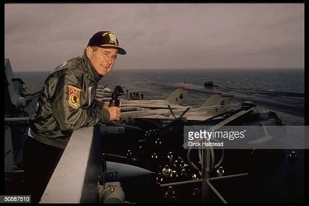 USS Forrestal cap jacketclad Pres Bush perching above war planereplete aircraft carrier flight deck taking break fr USSoviet summit