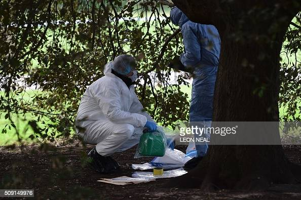 A forsensics officer holds a plastic fuel cannister in an evidence bag under a tree close to the scene where a man died after being discovered on...