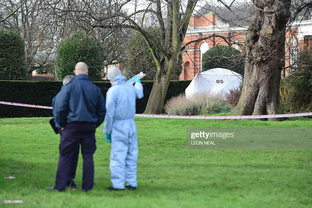 A forsensics officer in overalls gestures toward the tent errected over the scene where a man died after being discovered on fire in the park outside...