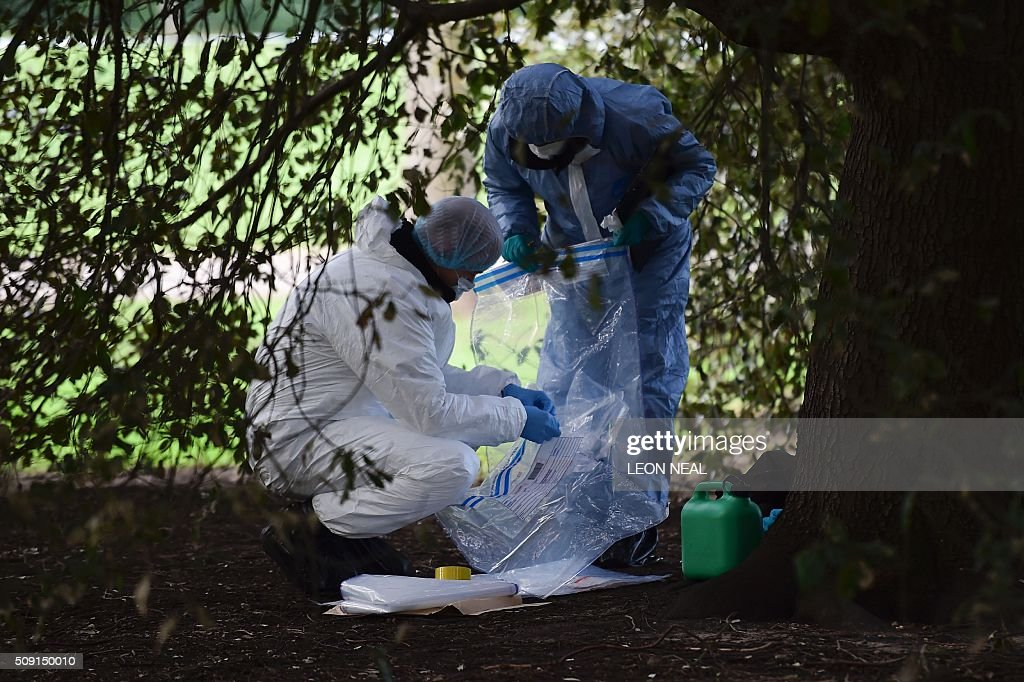 Forsensics officers afix a label to an evidence bag with a plastic fuel cannister on the floor by them as they work behind a police cordon under a...