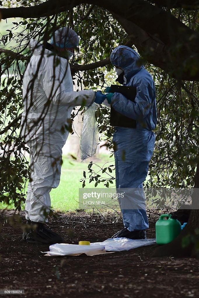 Forsensics officers handle evidence bags with a plastic fuel cannister on the floor by them as they work behind a police cordon under a tree close to the scene where a man died after being discovered on fire in the park outside the wall of Kensington Palace in London on February 9, 2016. A man has died after being found on fire outside Kensington Palace in the early hours of February 9, police said. Officers were called to the London home of the Duke and Duchess of Cambridge after receiving reports a man was behaving suspiciously. On arrival a man was found on fire and despite efforts from officers and paramedics the man was pronouced dead at the scene. NEAL