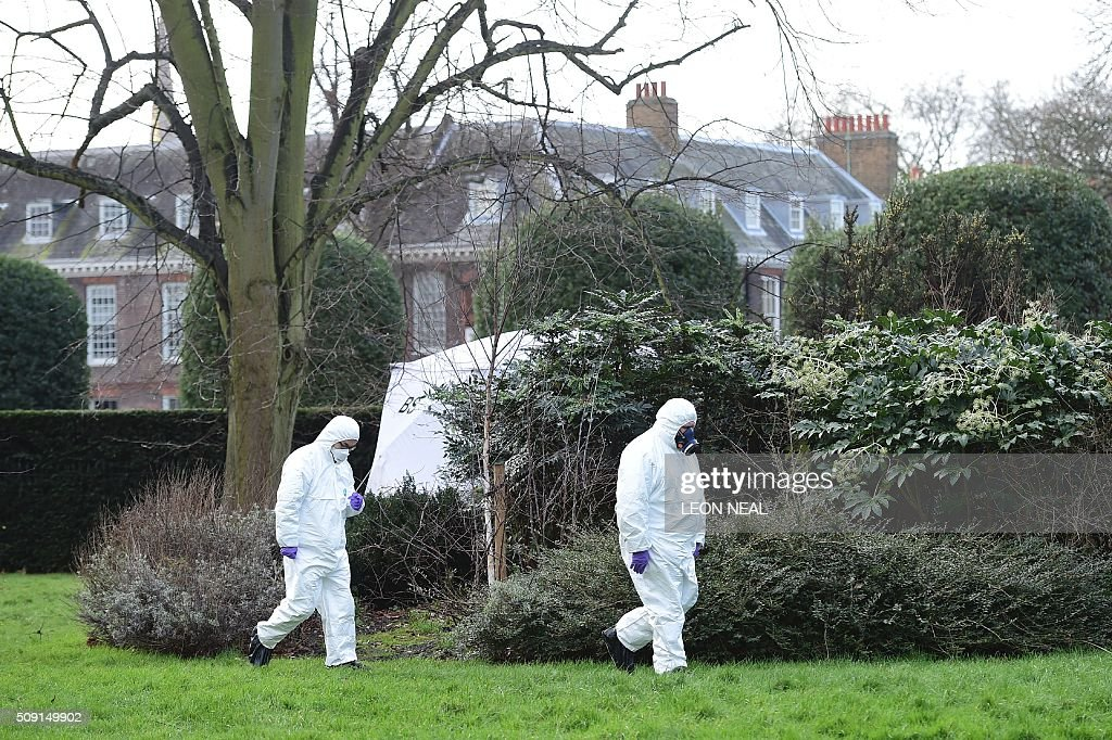 Forsensics officers in overalls and masks walk by the tent errected over the scene where a man died after being discovered on fire in the park outside the wall of Kensington Palace in London on February 9, 2016. A man has died after being found on fire outside Kensington Palace in the early hours of February 9, police said. Officers were called to the London home of the Duke and Duchess of Cambridge after receiving reports a man was behaving suspiciously. On arrival a man was found on fire and despite efforts from officers and paramedics the man was pronouced dead at the scene. NEAL