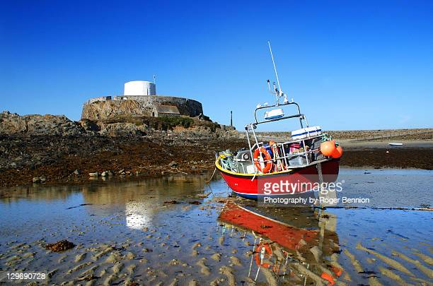 Fort grey and reflected fishing boat