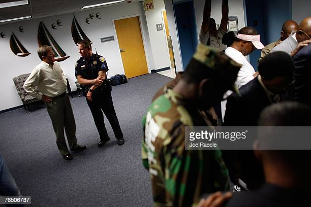 Fort Lauderdale Mayor Jim Naugle talks to a police officer as supporters most of whom are religious clergy bow their heads in prayer after a meeting...
