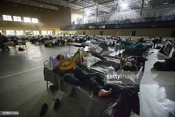 A Fort McMurray evacuee plays a guitar while lying on a cot at a hockey rink in Lac La Biche Alberta Canada on Saturday May 7 2016 Wildfires ravaging...