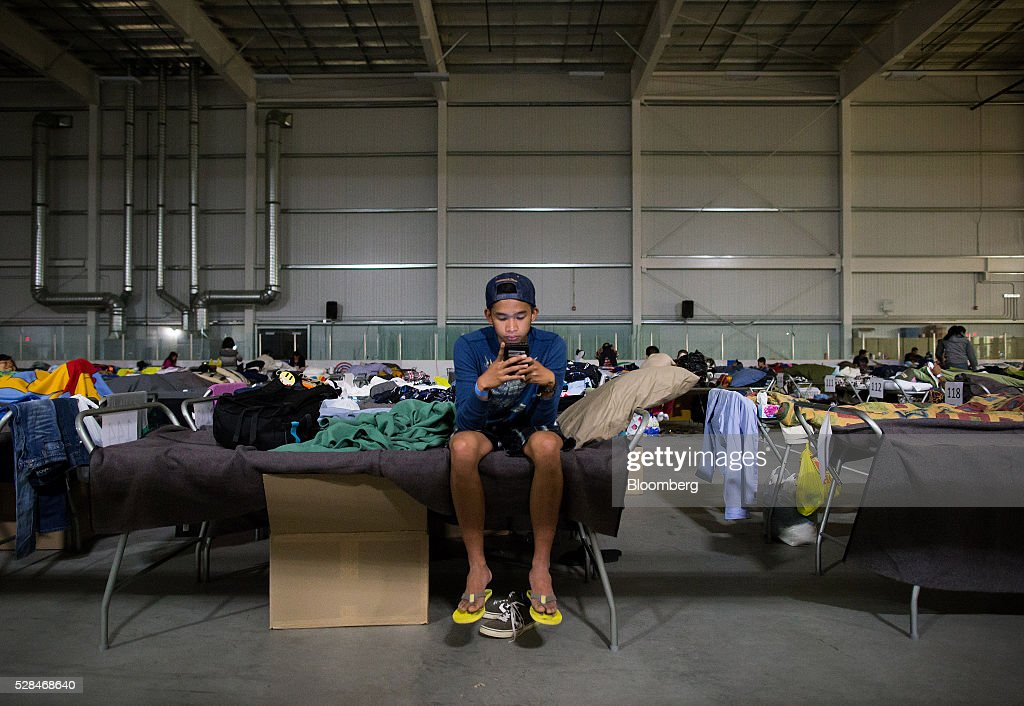 A Fort McMurray wildfire evacuee looks at his phone while sitting on a cot at a hockey rink in Lac La Biche, Alberta, Canada, on Thursday, May 5, 2016. A fire fueled by shifting winds that forced more than 80,000 people to flee their homes and threatened the business district of oil-sands hub Fort McMurray, Canada, raged out of control Wednesday after consuming 80 square kilometers (30 square miles) of land and damaging 1,600 buildings. Photographer: Darryl Dyck/Bloomberg via Getty Images