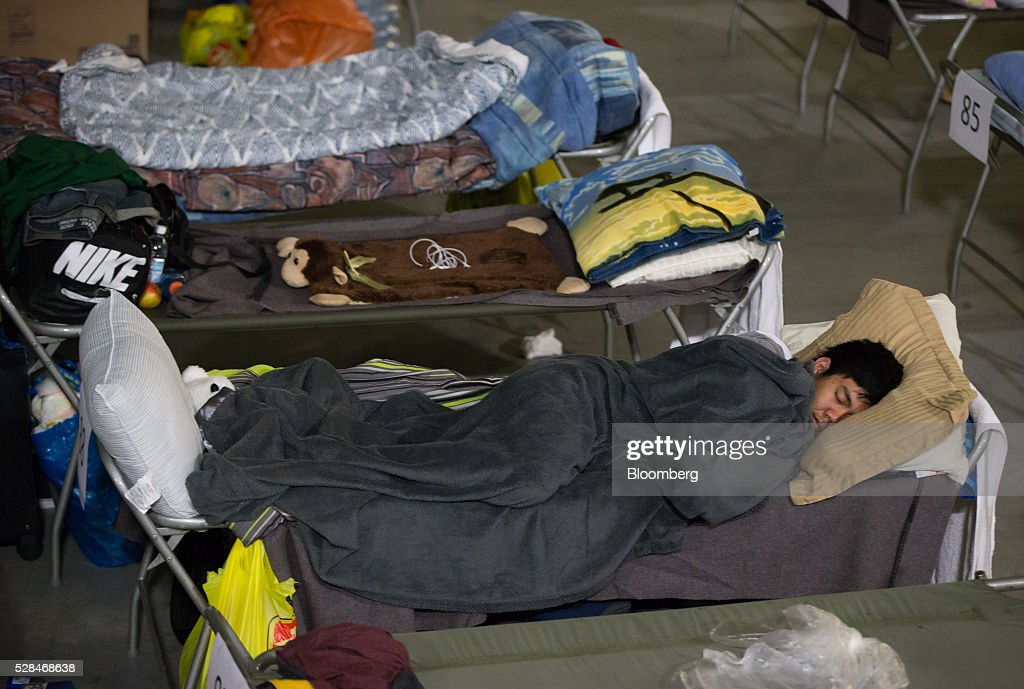 A Fort McMurray wildfire evacuee sleeps on a cot at a hockey rink in Lac La Biche, Alberta, Canada, on Thursday, May 5, 2016. A fire fueled by shifting winds that forced more than 80,000 people to flee their homes and threatened the business district of oil-sands hub Fort McMurray, Canada, raged out of control Wednesday after consuming 80 square kilometers (30 square miles) of land and damaging 1,600 buildings. Photographer: Darryl Dyck/Bloomberg via Getty Images