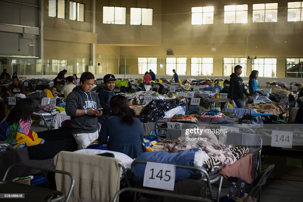 Fort McMurray wildfire evacuees gather around cots at a hockey rink in Lac La Biche, Alberta, Canada, on Thursday, May 5, 2016. A fire fueled by shifting winds that forced more than 80,000 people to flee their homes and threatened the business district of oil-sands hub Fort McMurray, Canada, raged out of control Wednesday after consuming 80 square kilometers (30 square miles) of land and damaging 1,600 buildings. Photographer: Darryl Dyck/Bloomberg via Getty Images