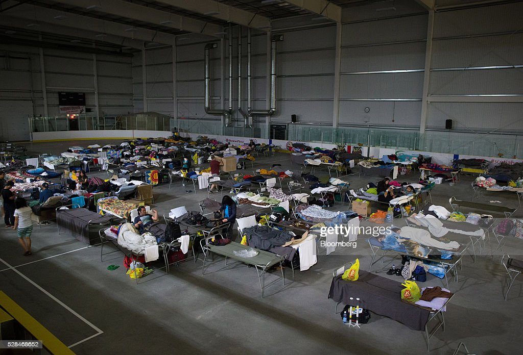 Fort McMurray wildfire evacuees lie on cots at a hockey rink in Lac La Biche, Alberta, Canada, on Thursday, May 5, 2016. A fire fueled by shifting winds that forced more than 80,000 people to flee their homes and threatened the business district of oil-sands hub Fort McMurray, Canada, raged out of control Wednesday after consuming 80 square kilometers (30 square miles) of land and damaging 1,600 buildings. Photographer: Darryl Dyck/Bloomberg via Getty Images