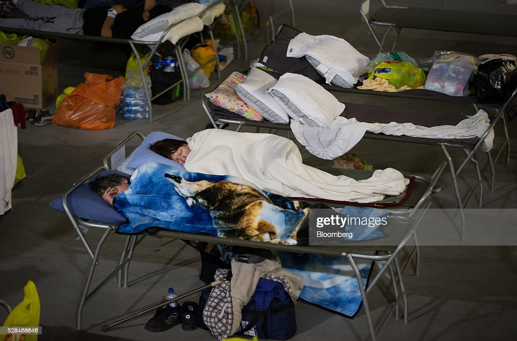 Fort McMurray wildfire evacuees sleep on cots at a hockey rink in Lac La Biche, Alberta, Canada, on Thursday, May 5, 2016. A fire fueled by shifting winds that forced more than 80,000 people to flee their homes and threatened the business district of oil-sands hub Fort McMurray, Canada, raged out of control Wednesday after consuming 80 square kilometers (30 square miles) of land and damaging 1,600 buildings. Photographer: Darryl Dyck/Bloomberg via Getty Images