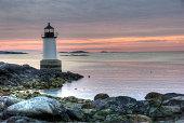 Rocky coastal shoreline with historical Fort Pickering Lighthouse.  Summer sunrise.