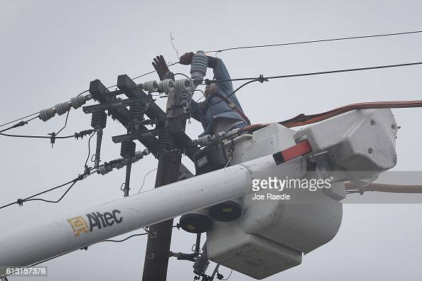 Fort Pierce Utilities worker works on an electrical line to restore power after Hurricane Matthew passed through the area on October 7 2016 in Fort...