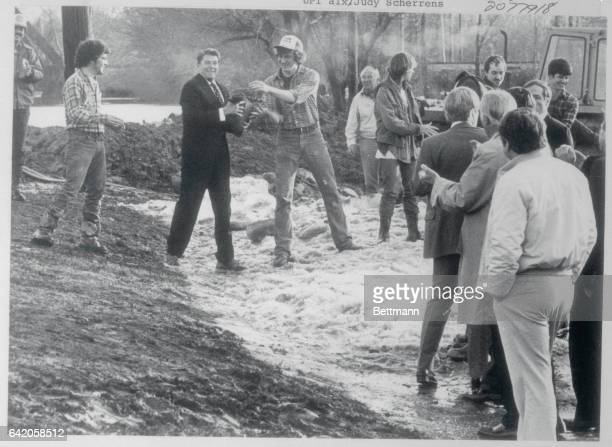 As Mayor Winfield Moses Jr and Governor Robert Orr watch President Ronald Reagan helps in a sand bag line in Fort Wayne The President and his aides...
