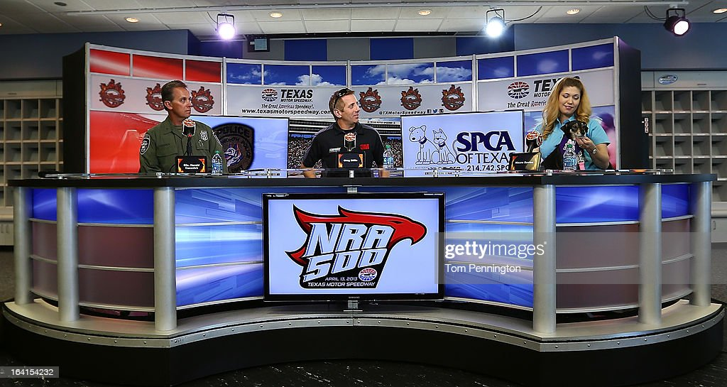 Fort Worth Police officer Harald Cussnick; Greg Biffle, driver of the #16 3M Ford Fusion; and Maura Davies, vice president of communication with the SPCA of Texas talk with the media during an event at Texas Motor Speedway on March 20, 2013 in Fort Worth, Texas.