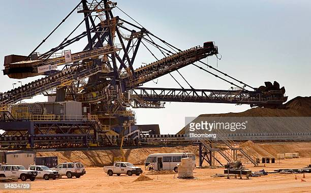 Fortescue Metals Group's iron ore is fed onto a conveyer belt for loading into an iron ore carrier in Port Hedland in the Pilbara region of Australia...