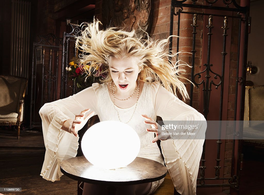 Fortune teller gazes in crystal ball. : Foto de stock