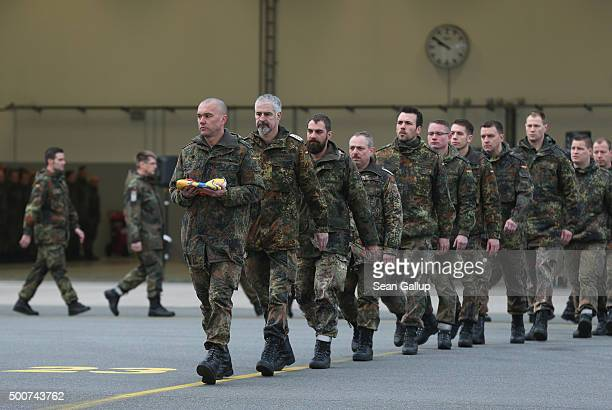 Forty members of the Bundeswehr the German armed forces including one clutching the state flag of SchleswigHolstein prepare to board a Luftwaffe...