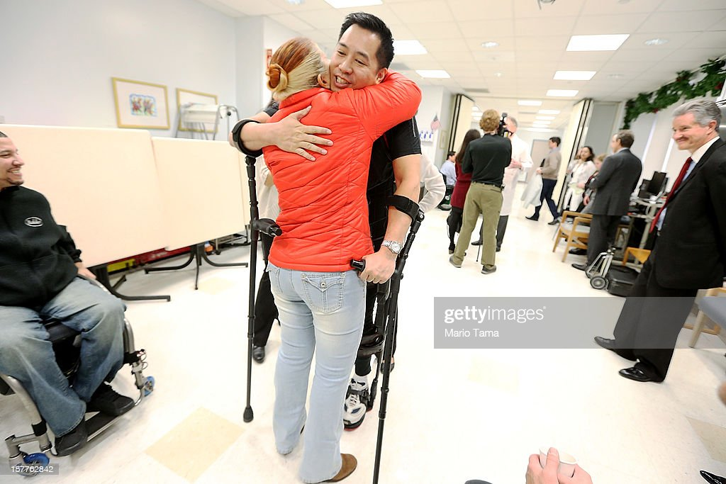 Forty three-year-old parapalegic Robert Woo hugs Deborah Kuryz while walking with an exoskeleton device made by Ekso Bionics during a demonstration at the opening of the Rehabilitation Bionics Program at Mount Sinai Rehabilitation Center on December 6, 2012 in New York City. Woo is an architect who was paralyzed from the hips down during a construction accident and thought he would never walk again. The new strap-on exoskelton uses motors and sensors to physically move the legs.
