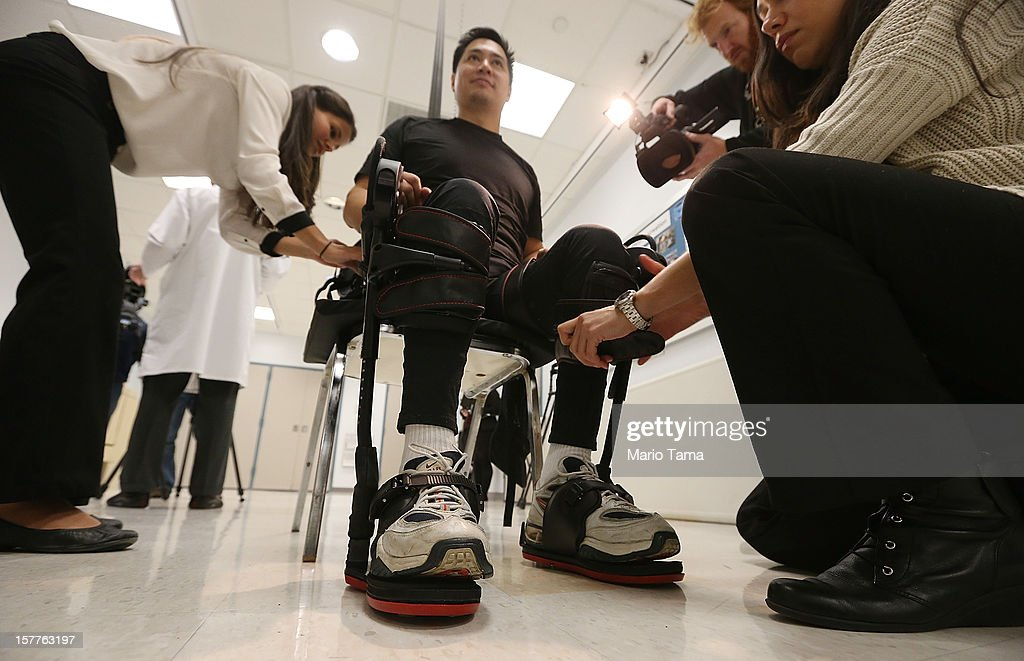 Forty three-year-old parapalegic Robert Woo is outfitted with an exoskeleton device to walk in made by Ekso Bionics as Manuel Maldonado (L) during a demonstration at the opening of the Rehabilitation Bionics Program at Mount Sinai Rehabilitation Center on December 6, 2012 in New York City. Woo is an architect who was paralyzed from the hips down during a construction accident and thought he would never walk again. The new strap-on exoskelton uses motors and sensors to physically move the legs.