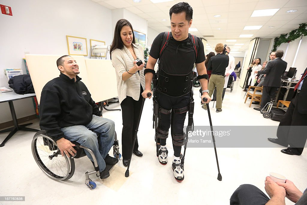 Forty three-year-old parapalegic Robert Woo walks with an exoskeleton device made by Ekso Bionics as Manuel Maldonado (L) looks on during a demonstration at the opening of the Rehabilitation Bionics Program at Mount Sinai Rehabilitation Center on December 6, 2012 in New York City. Woo is an architect who was paralyzed from the hips down during a construction accident and thought he would never walk again. The new strap-on exoskelton uses motors and sensors to physically move the legs.