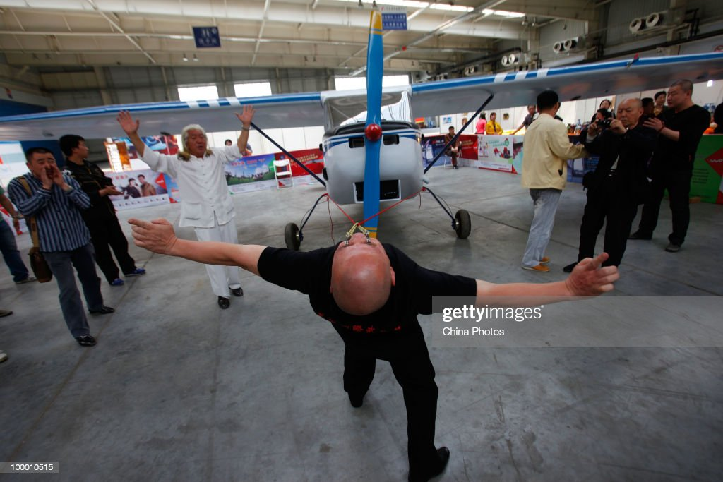 Forty-eight year old Dong Changsheng pulls a 560 kilograms (about 1,234.8 pounds) amphibian aircraft for about 5 meters (about 16.4 feet) through ropes hooked on his lower eyelids as he performs a stunt on May 20, 2010 in an exhibition center in Changchun of Jilin Province, China. Dong has performed stunts around the country since 1991 through the help of Qigong, a system of deep breathing exercises, according to local media.
