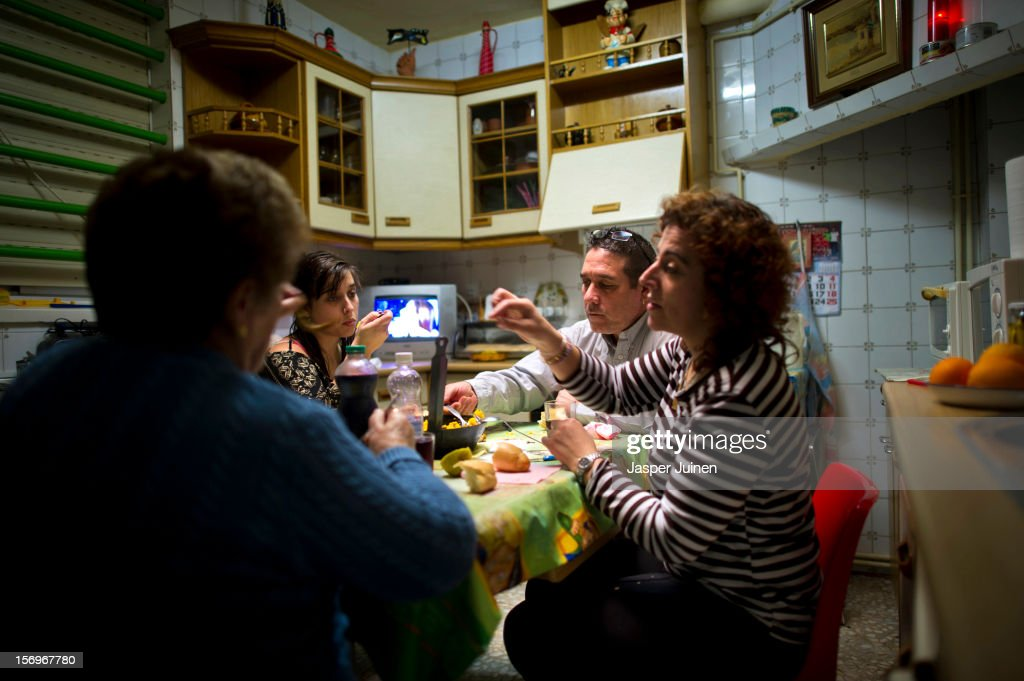 Forty-eight year old former door factory worker Angel Perez Fernandez (2nd R) eats Paella together with his forty-year old wife, Maria Regine Bueno Villar (R), who worked as a cleaning lady at door factories, and their unemployed twenty-year daughter Maria Regina (2nd L), at the home of his mother in law on November 23, 2012 in Villacanas, Spain. During the boom years, where in its peak Spain built some 800,000 houses a year accompanied by the manufacturing of millions of wooden doors where needed, the people of Villacanas were part of Spain's middle class enjoying high wages and permanent jobs. During the construction boom years the majority of the doors used within these new developments were made in this small industrial town. Approximately seven million doors a year were once assembled here and the factory employed a workforce of almost 5700 people, but the town is now left almost desolate with the Villacanas industrial park now empty and redundant. With Spain in the grip of recession and the housing bubble burst, Villacanas is typical of many former buoyant industrial Spanish towns now struggling with huge unemployment problems.