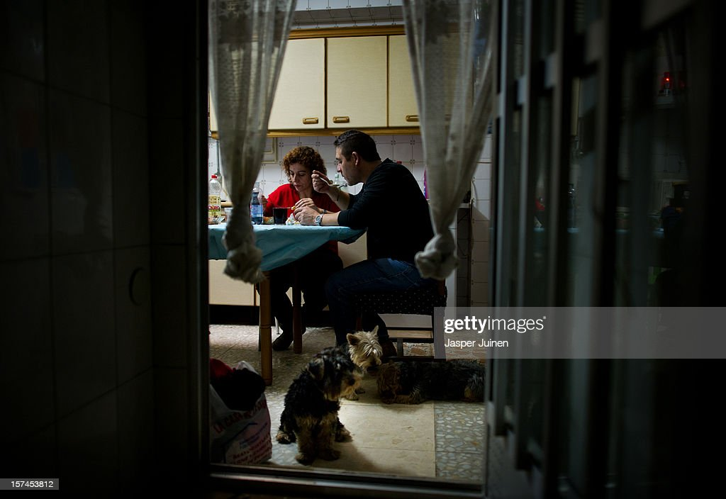 Forty-eight year old former door factory worker Angel Perez Fernandez (R) eats lunch with his forty-year old wife, Maria Regine Bueno Villar, who worked as a cleaning lady at door factories, accompagnied by their dogs at the home of his mother in law on November 30, 2012 in Villacanas, Spain. During the boom years, where in its peak Spain built some 800,000 houses a year accompanied by the manufacturing of millions of wooden doors, the people of Villacanas were part of Spain's middle class enjoying high wages and permanent jobs. During the construction boom years the majority of the doors used within these new developments were made in this small industrial town. Approximately seven million doors a year were once assembled here and the factories employed a workforce of almost 5700 people, but the town is now left almost desolate with the Villacanas industrial park now empty and redundant. With Spain in the grip of recession and the housing bubble burst, Villacanas is typical of many former buoyant industrial Spanish towns now struggling with huge unemployment problems.