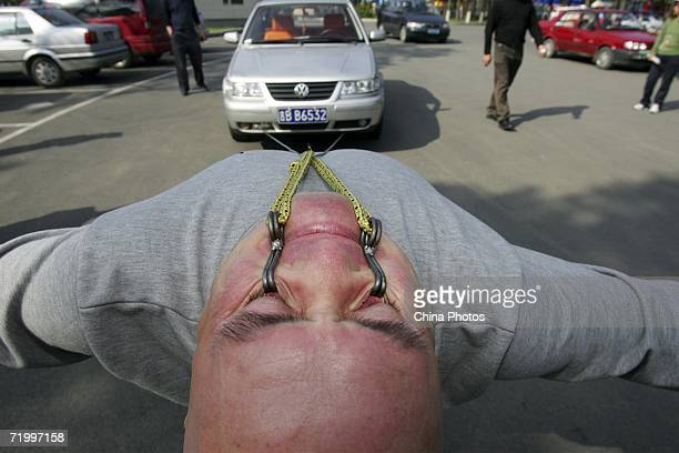 Fortyfour year old Dong Changsheng of China pulls a 15 ton car for about 10 meters through ropes hooked on his lower eyelids as he performs a stunt...