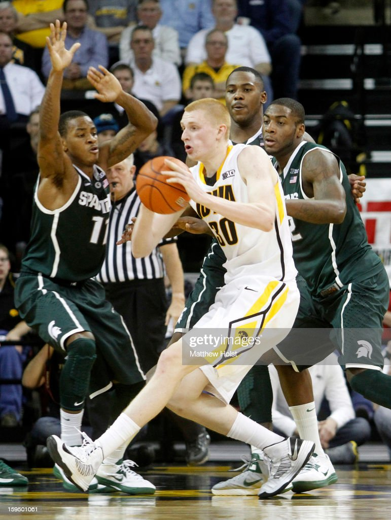 Forward Aaron White #30 of the Iowa Hawkeyes drives to the basket during the second half against guards Keith Appling #11 and Branden Dawson #22 of the Michigan State Spartans on January 10, 2013 at Carver-Hawkeye Arena in Iowa City, Iowa. Michigan State won 62-59.