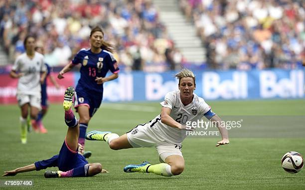 USA forward Abby Wambach is tackled by Japan's midfielder Homare Sawa during the final football match between USA and Japan during their 2015 FIFA...