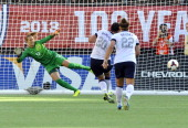 Forward Abby Wambach of the US Women's National Team is backed up by midfielder Amber Brooks as she scores on a penalty kick against goalkeeper...