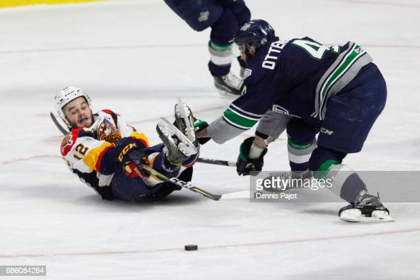 Forward Alex DeBrincat of the Erie Otters battles for the puck after a hit from defenceman Turner Ottenbreit of the Seattle Thunderbirds on May 20...