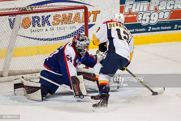 Forward Alex DeBrincat of the Erie Otters slides the puck past goaltender Michael DiPietro of the Windsor Spitfires on February 6 2016 at the WFCU...