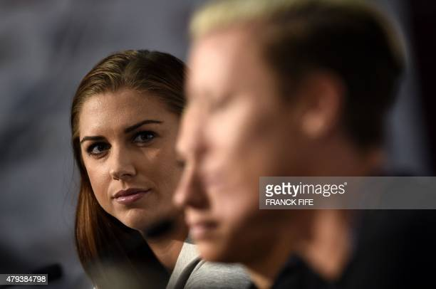 USA forward Alex Morgan and midfielder Carli Lloyd look on as forward Abby Wambach speaks during a press conference in Vancouver on July 3 two days...