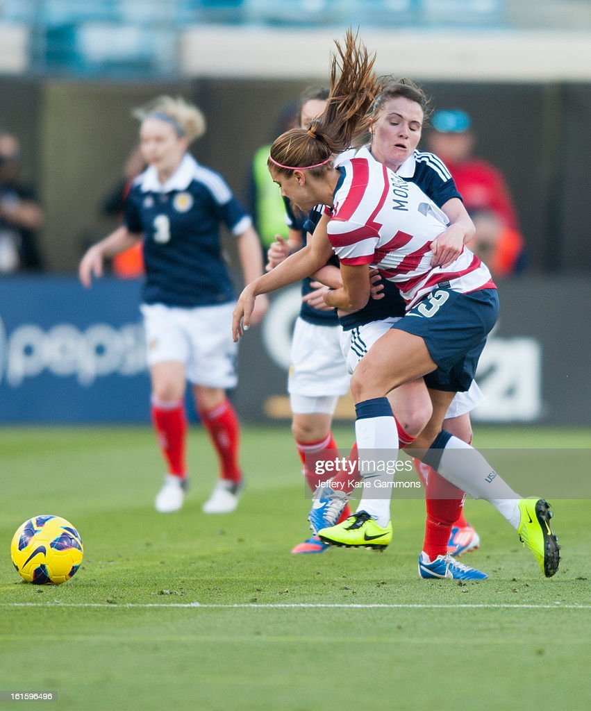 Forward Alex Morgan #13 of the United States and Midfielder Joanne Love #6 of Scotland collide during the game at EverBank Field on February 9, 2013 in Jacksonville, Florida.