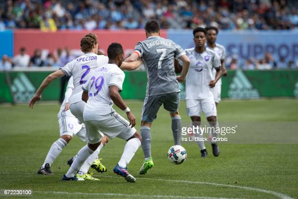 Forward and Captain David Villa of New York City FC gives a slight back kick to avoid Jonathan Spector and Tommy Redding of Orlando City SC during...
