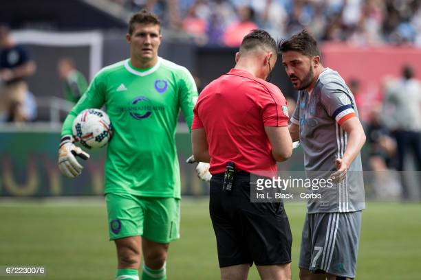 Forward and Captain David Villa of New York City FC has a discussion with the referee about his yellow card with Joe Bendik of Orlando City SC...